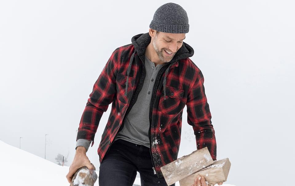 Mann in Schnee Winter Style angezogen mit Feuerholz in der Hand